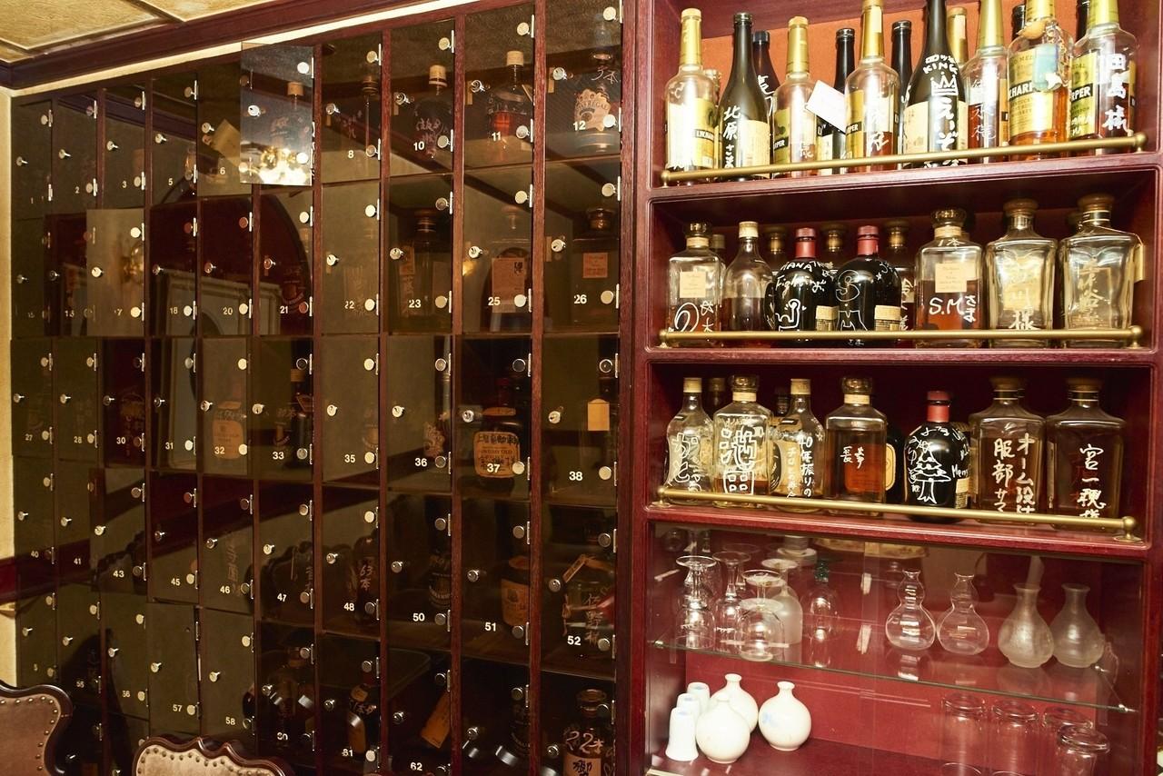 スナックの壁に配置されたボトルロッカー。
