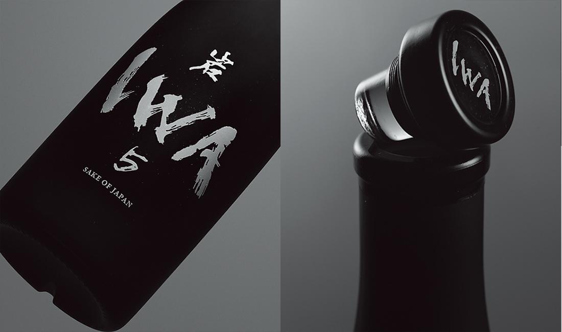 黒いすりガラスのボトルに、書道家、木下真理子の筆による白い「IWA」の文字。